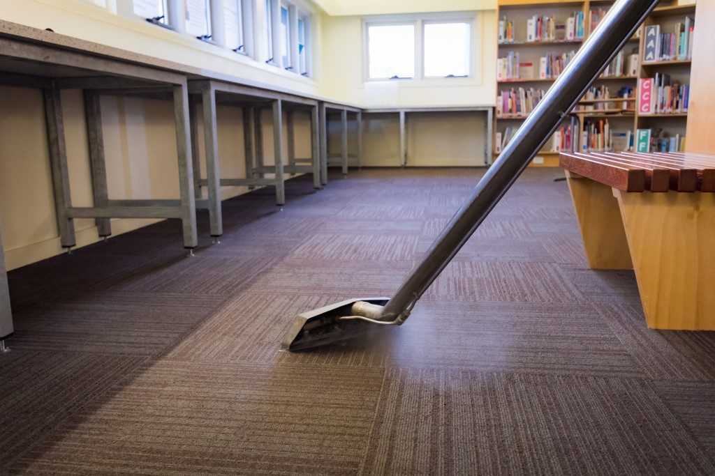 Vacuuming the carpet of the library