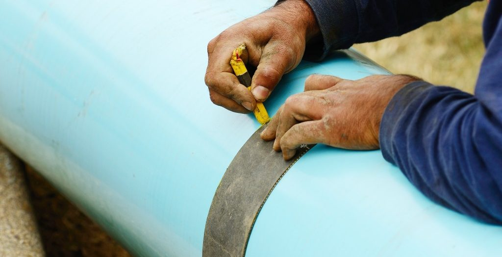 Employee measuring a water pipe