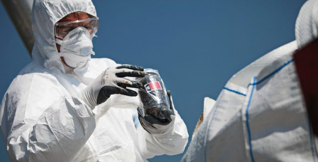 Health personnel holding a plastic with asbestos