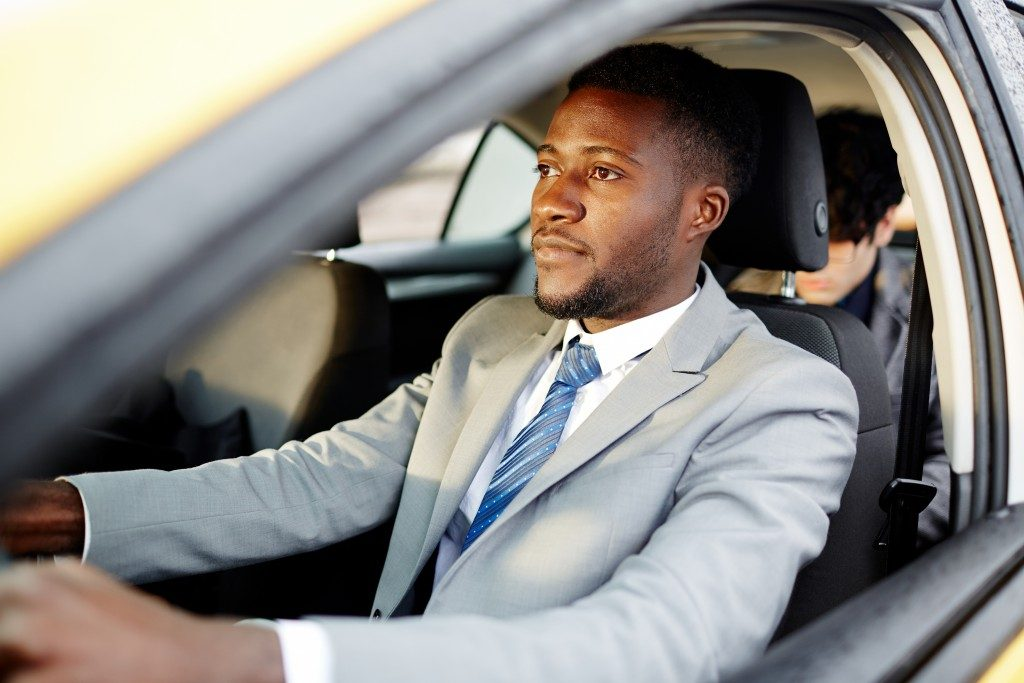 man in a suit driving a car