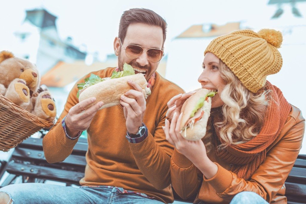 two people enjoying eating a sandwich outdoors