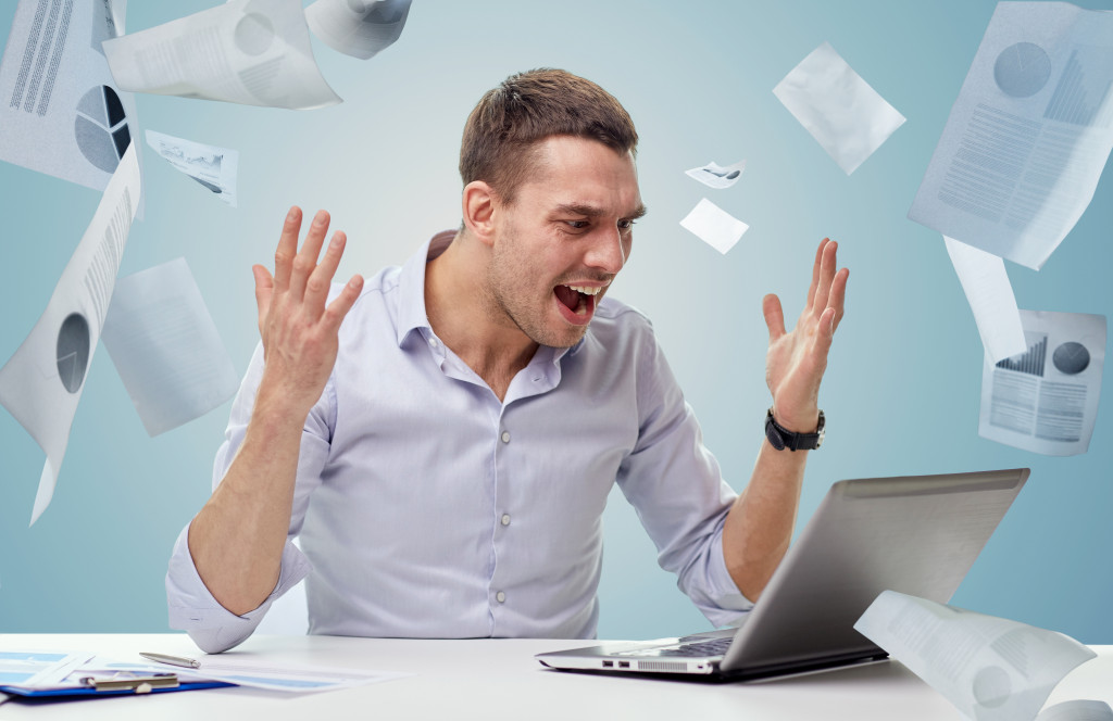 man stressed from work throwing papers